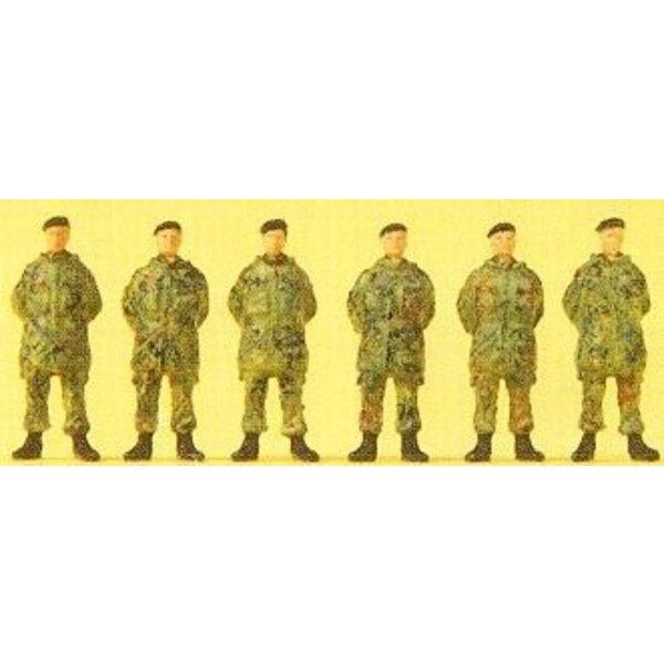 Soldado de pie, con boina y chaqueta de camuflaje
